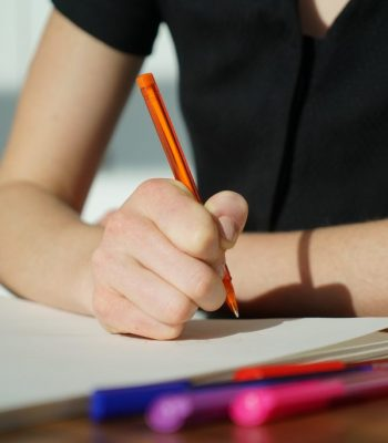 Woman writes a note with an orange pen